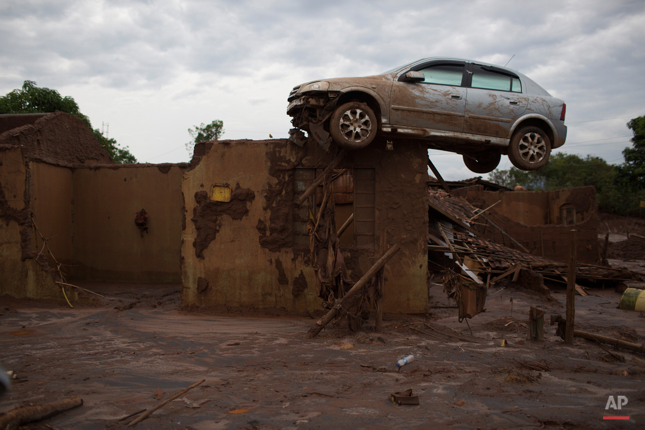 In this Nov. 23, 2015 photo, a car sits precariously on top of the wall of a home, destroyed when the dam of an iron ore mine burst in early November, causing a mudslide, in Bento Rodrigues, Brazil. Thirteen people died in the tragedy, and another 11 remain missing. (AP Photo/Leo Correa)