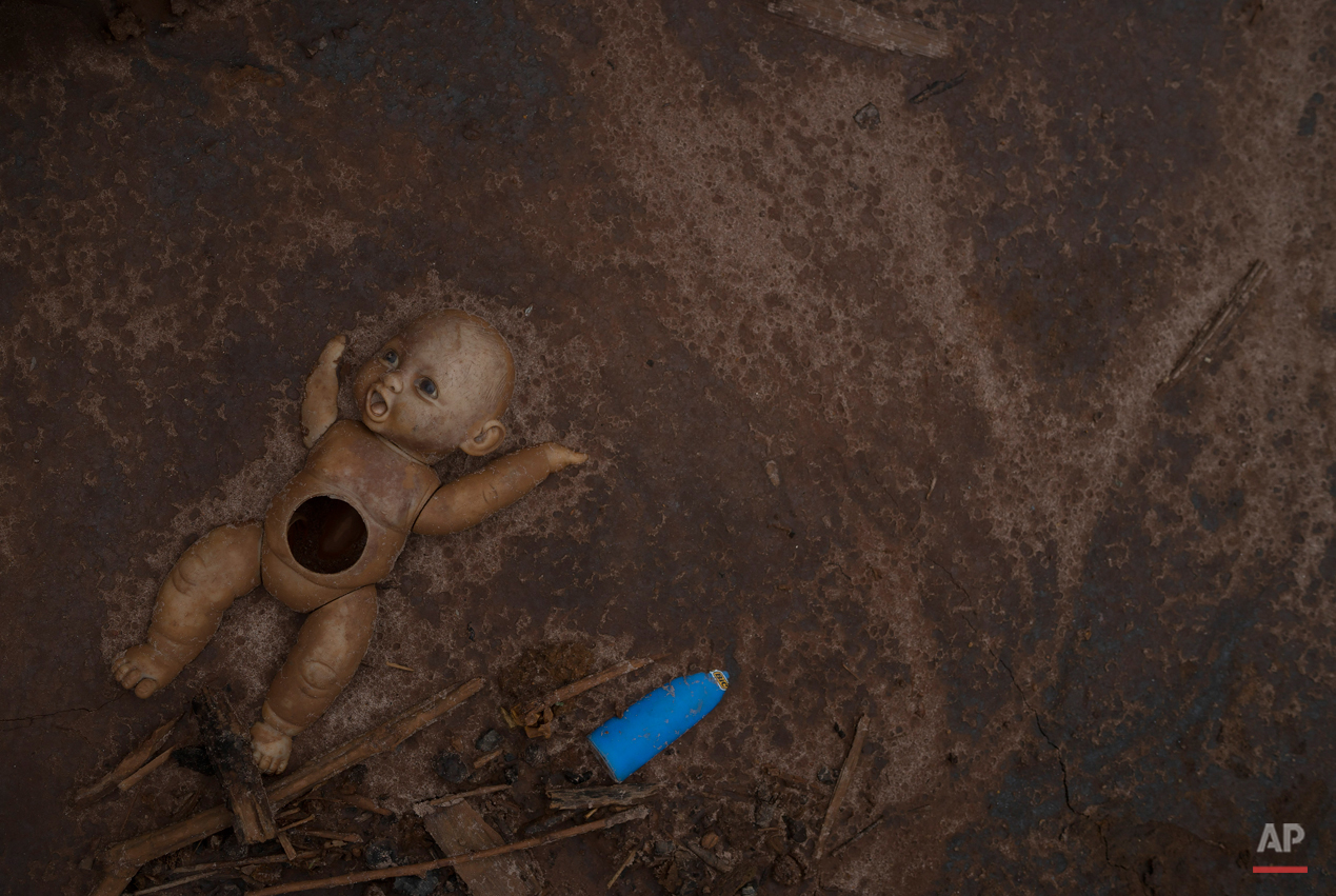 In this Nov. 24, 2015 photo, a doll lies embedded in a layer of mud in Paracatu, Brazil. Thirteen people died in the tragedy, and another 11 remain missing. (AP Photo/Leo Correa)