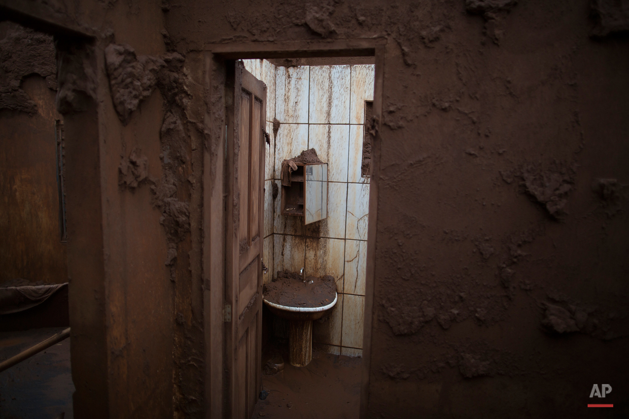 This Nov. 23, 2015 photo, shows the walls of a home covered in mud, damaged when a dam that burst at the nearby iron ore mine caused a mudslide, in Bento Rodrigues, Brazil. With hundreds of survivors holed up in hotels and with family members in nearby towns, Bento Rodrigues and other nearby hamlets like Paracatu have become ghost towns. (AP Photo/Leo Correa)