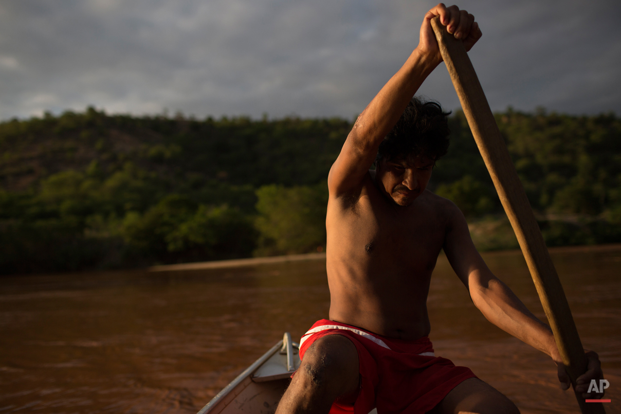 """In this Nov. 22, 2015 photo, Ererre, of the Krenak people, rows his boat in the now polluted Doce River, contaminated by a mix of residues from a dam that burst in early November, in Resplendor, Brazil. """"Here we used to have a lot of fish that we liked. Now, our river is dead, our river is over. Our fish are dead, everything is dead."""" Errere said. (AP Photo/Leo Correa)"""