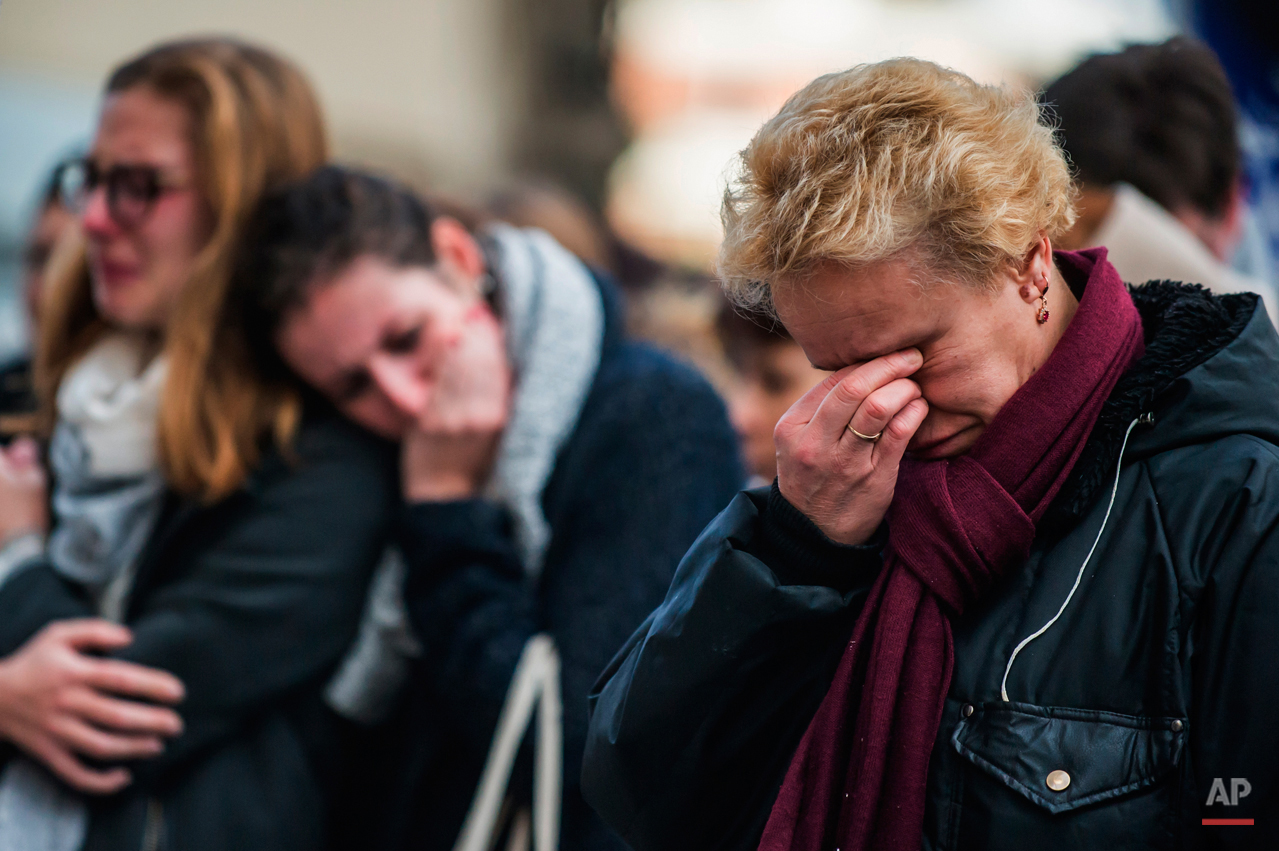 People react in front of the restaurant Le Carillon Nov. 16, 2015, one of the establishments targeted in the Nov. 13, 2015 terrorist attacks in Paris. (AP Photo/Kamil Zihnioglu)