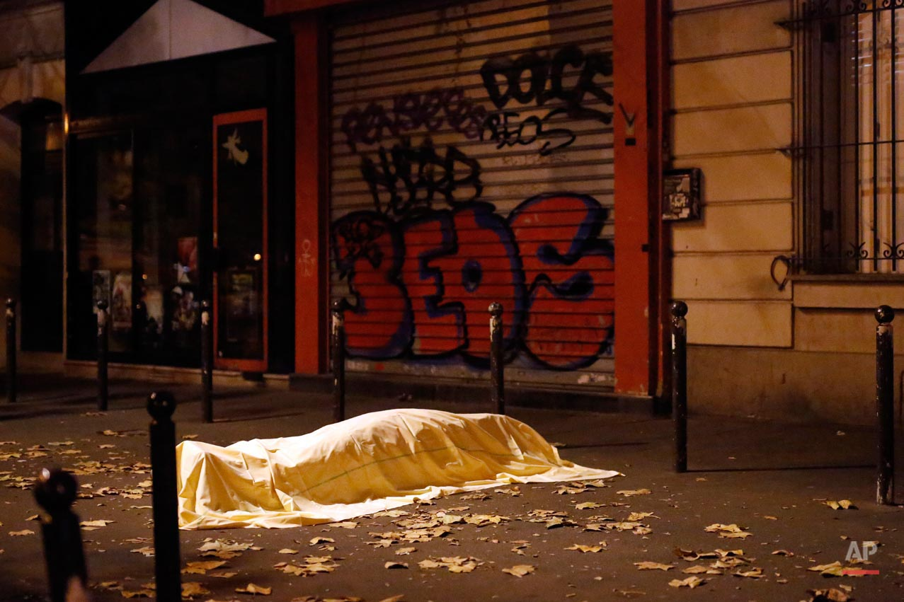 A victim of a terrorist attack lays dead outside the Bataclan theater in Paris, Nov. 13, 2015. (AP Photo/Jerome Delay)