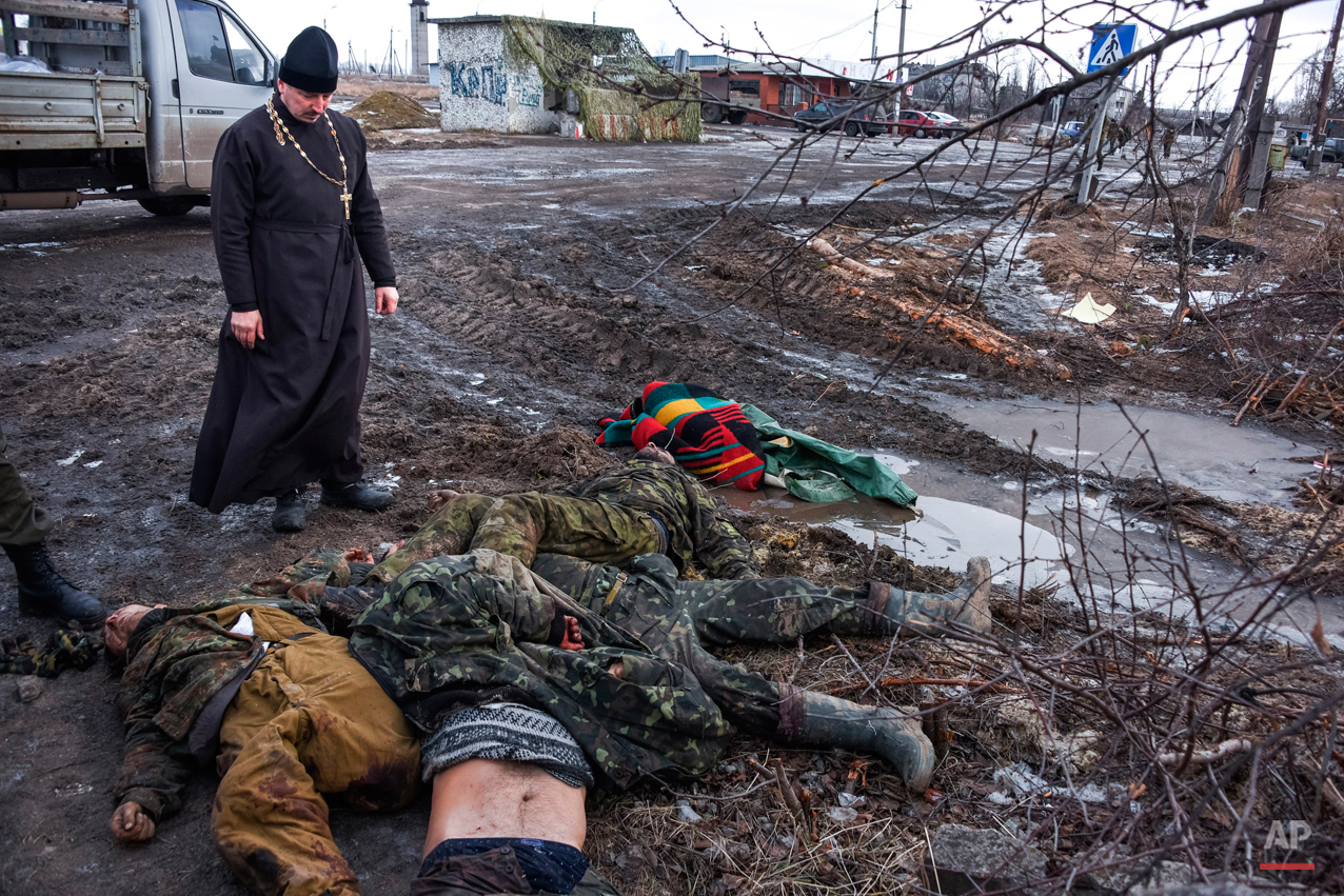 An Orthodox priest stands next to the bodies of killed Ukrainian soldiers on a check-point captured by pro-Russian rebels at the town of Krasniy Partizan, eastern Ukraine, Saturday, Jan. 24, 2015. The fighting continues despite several cease fire declarations. (AP Photo/Mstyslav Chernov)