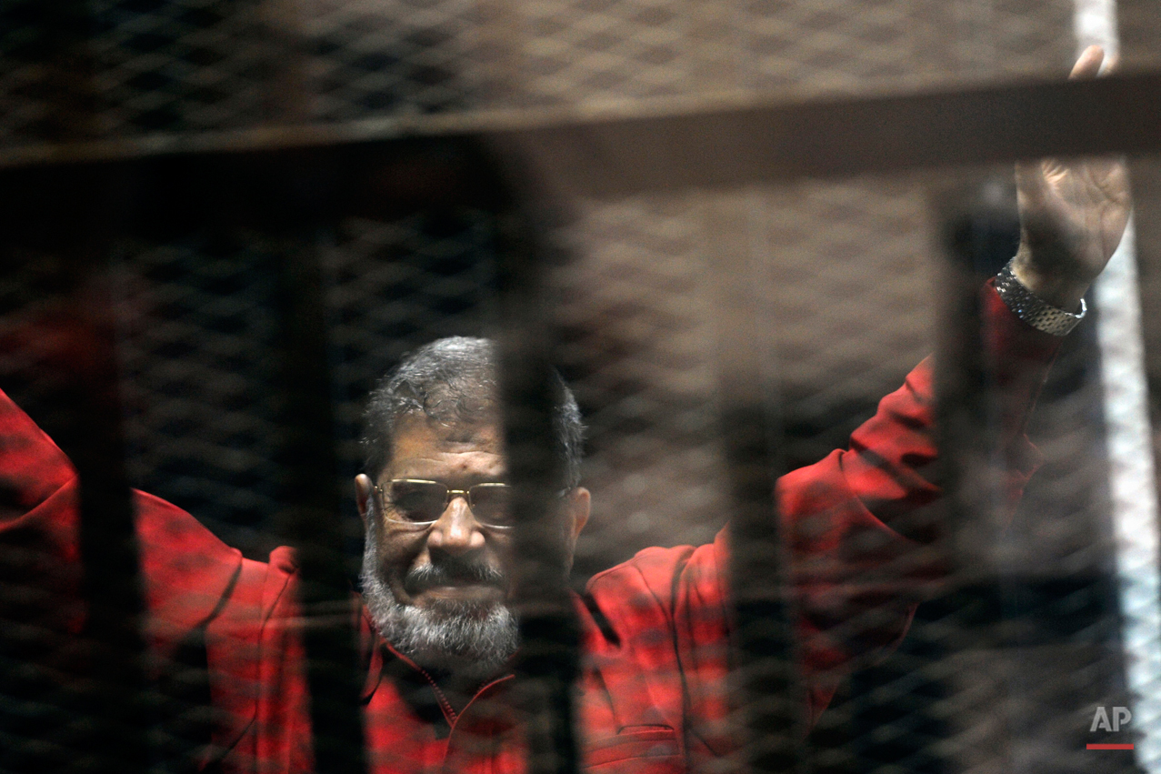 Ousted Egyptian President Mohammed Morsi, wearing a red jumpsuit that designates he has been sentenced to death, raises his hands inside a defendants cage in a makeshift courtroom at the national police academy, in an eastern suburb of Cairo, Egypt, Sunday, June 21, 2015. An Egyptian court held a hearing for a case in which Morsi and ten others are charged with leaking classified documents to Qatar. A court last week sentenced Morsi to death in a separate case over a prison break in 2011. (AP Photo/Ahmed Omar)