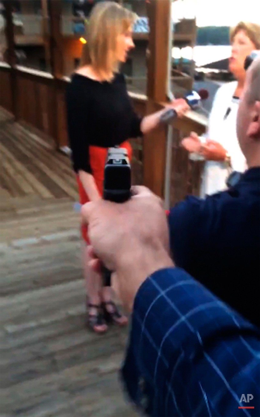In this framegrab from video posted on Bryce Williams' Twitter account and Facebook page, Williams, whose real name is Vester Lee Flanagan II, aims a gun over the shoulder of WDBJ-TV cameraman Adam Ward at reporter Alison Parker as she conducts a live on-air interview Aug. 26, 2015. Moments later, Flanagan fatally shot Parker and Ward and injured Vicki Gardner, who was being interviewed. The station said Flanagan was also an employee at WDBJ and appeared on air as Bryce Williams. (Vester Lee Flanagan II/Twitter via AP)