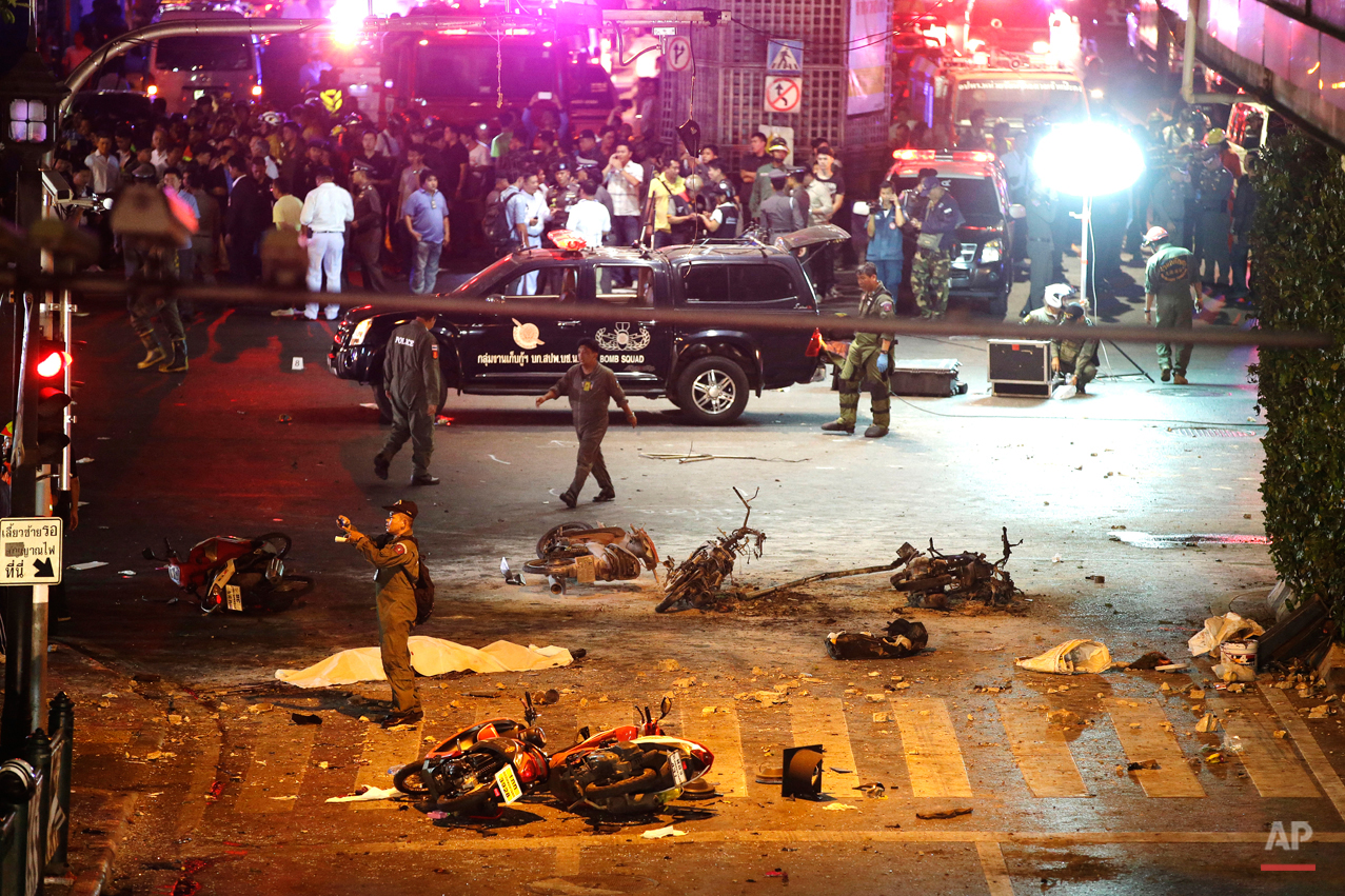A policeman photographs debris from an explosion in central Bangkok, Thailand, Monday, Aug. 17, 2015. A large explosion rocked a central Bangkok intersection during the evening rush hour, killing a number of people and injuring others, police said. (AP Photo/Mark Baker)