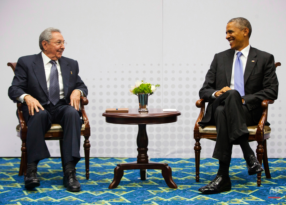 US President Barack Obama, right, smiles as he looks over towards Cuban President Raul Castro, left, during their meeting at the Summit of the Americas in Panama City, Panama, Saturday, April 11, 2015. The leaders of the United States and Cuba held their first formal meeting in more than half a century, clearing the way for a normalization of relations that had seemed unthinkable to both Cubans and Americans for generations. (AP Photo/Pablo Martinez Monsivais)