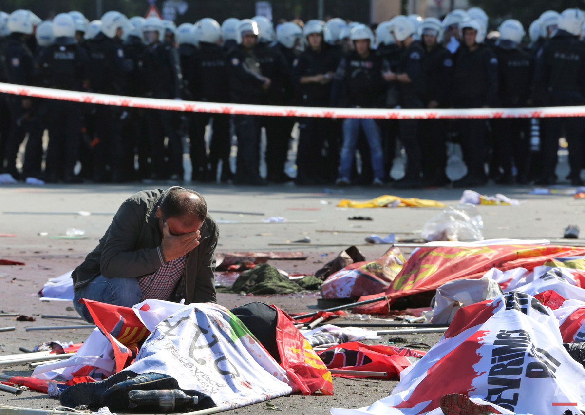 A man cries over the body of a victim, at the site of an explosion in Ankara, Turkey, Saturday, Oct. 10, 2015. The two bomb explosions targeting a peace rally in the capital Ankara killed dozens of people and injured scores of others. The explosions occurred minutes apart near Ankara's main train station as people were gathering for the rally, organized by the country's public sector workers' trade union and other civic society groups. The rally aimed to call for an end to the renewed violence between Kurdish rebels and Turkish security forces. (AP Photo/Burhan Ozbilici)