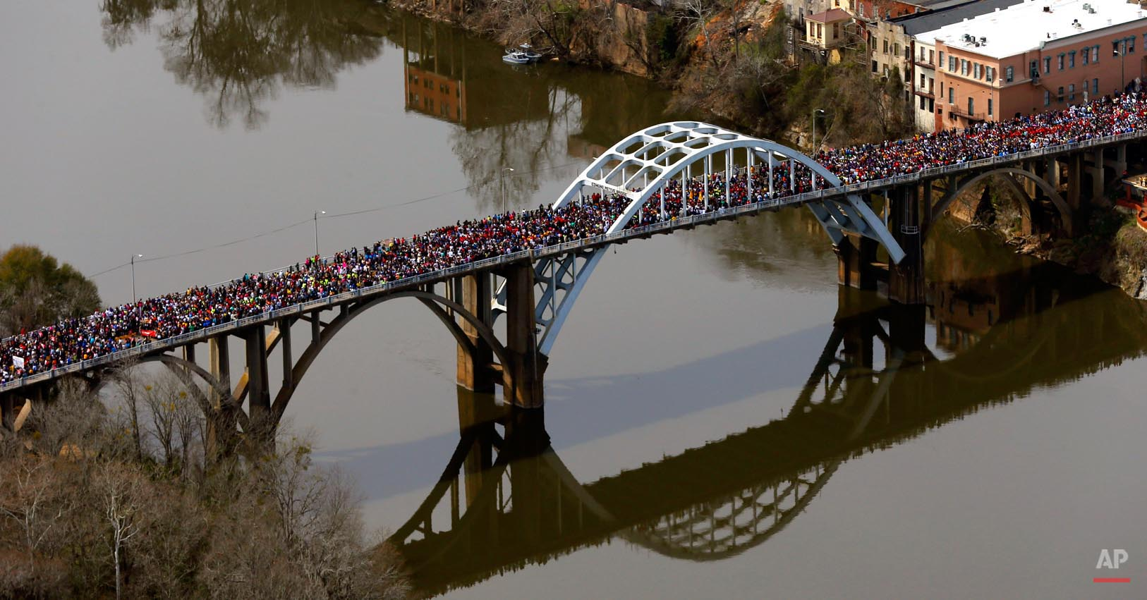"Crowds of people move in a symbolic walk across the Edmund Pettus Bridge, Sunday, March 8, 2015, in Selma, Ala. It marked the 50th anniversary of ""Bloody Sunday,"" a civil rights march in which protestors were beaten, trampled and tear-gassed by police at the Edmund Pettus Bridge, in Selma. (AP Photo/Butch Dill)"