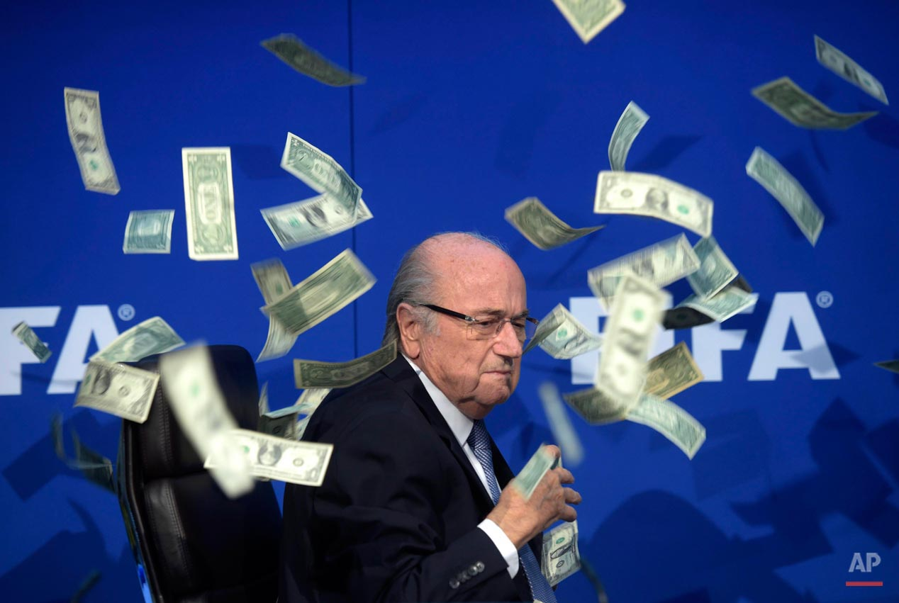 FIFA president Sepp Blatter is photographed while banknotes thrown by British comedian Simon Brodkin hurtle through the air during a press conference following the extraordinary FIFA Executive Committee at the headquarters in Zurich, Switzerland, Monday, July 20, 2015. During the extraordinary FIFA Executive Committee meeting the agenda for the elective Congress for the FIFA presidency was finalized and approved: The congress will take place on Feb. 26. 2016. (Ennio Leanza/Keystone via AP)