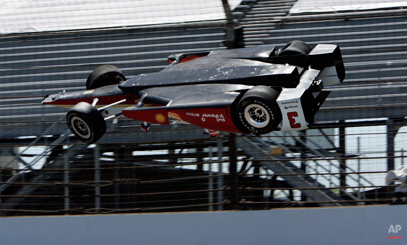 The car driven by Helio Castroneves, of Brazil, is airborne after hitting the wall in the first turn during practice for the Indianapolis 500 auto race at Indianapolis Motor Speedway in Indianapolis, Wednesday, May 13, 2015. (AP Photo/Joe Watts)
