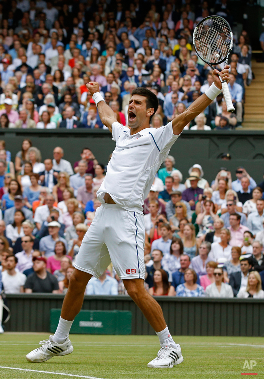 Novak Djokovic of Serbia celebrates winning the men's singles final against Roger Federer of Switzerland at the All England Lawn Tennis Championships in Wimbledon, London, Sunday July 12, 2015. Djokovic won the match 7-6, 6-7, 6-4, 6-3. (AP Photo/Alastair Grant)