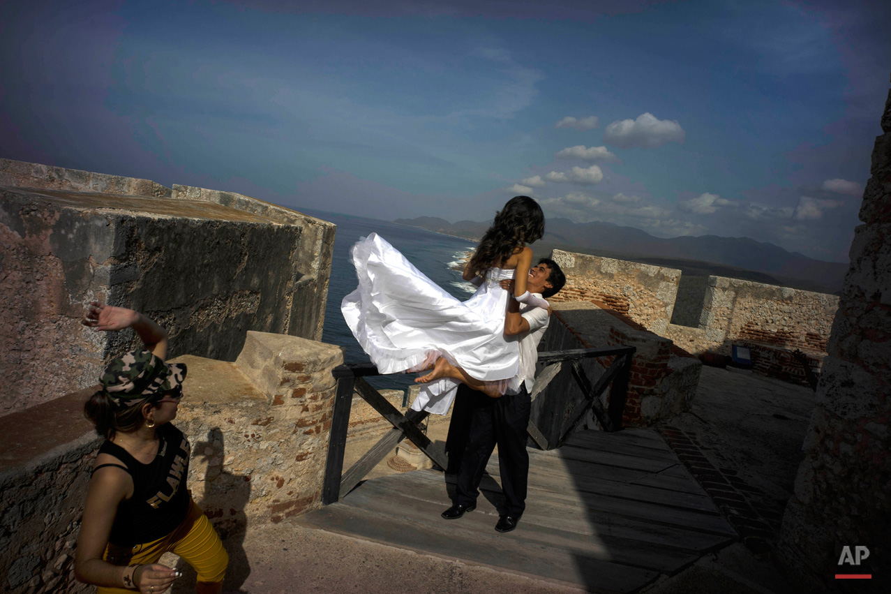 In this July 27, 2015, photo, newlyweds pose for photos during their photo session at the fortress of the Morro in Santiago. While Cuban cities are seeing stagnant visitor numbers, cruise ships provide a promising new potential source of visitors, although dockings remain relatively rare. (AP Photo/Ramon Espinosa)