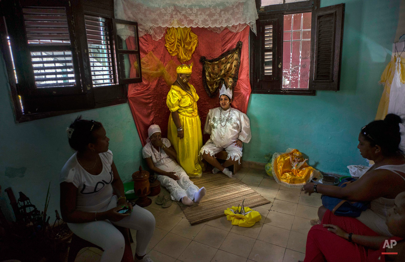"In this Sept. 11, 2015, photo, Marisa Ramirez Gutierrez, standing center, holds still on her throne dressed in the robe of the the ""Iyawo,"" or bride, alongside a pregnant woman, right, who represents birth, and her mother, who represents a woman who has already given birth, inside her home as part of many initiation ceremonies marking the start of her one-year journey to become a Yoruba priestess in Havana, Cuba. Ramirez's other initiation rituals include a dip in a river, sitting for one day with a pregnant woman, private rituals with Yoruba priests, a celebratory dinner party with family and friends, praying to the Virgin of Charity and leaving herbal offerings at a local market. (AP Photo/Ramon Espinosa)"