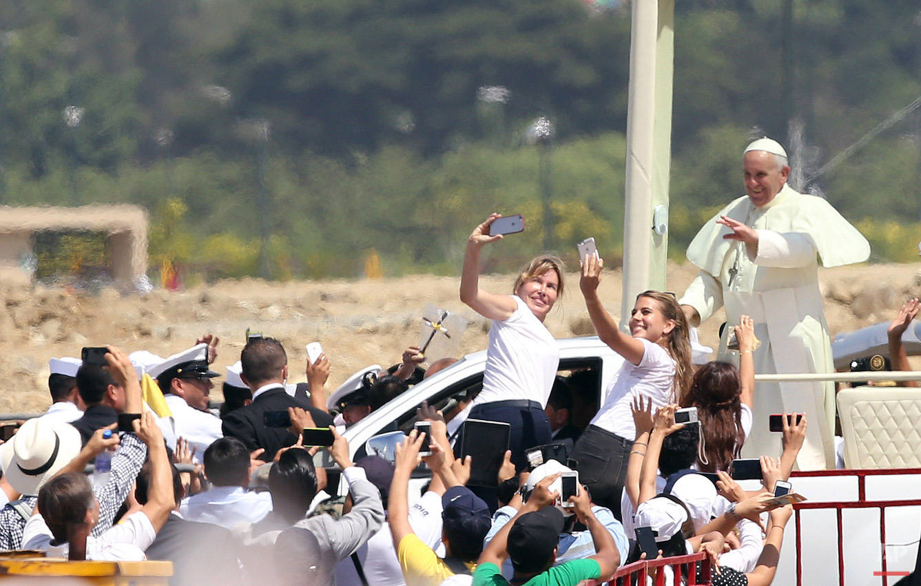 In this July 6, 2015, photo, Pope Francis waves to the crowd as he rides in the popemobile through Samanes Park, where he will celebrate Mass, in Guayaquil, Ecuador. A crowd estimated at 1 million people, greeted Francis on the packed dirt of Samanes Park for a late-morning Mass. (AP Photo/Fernando Vergara)