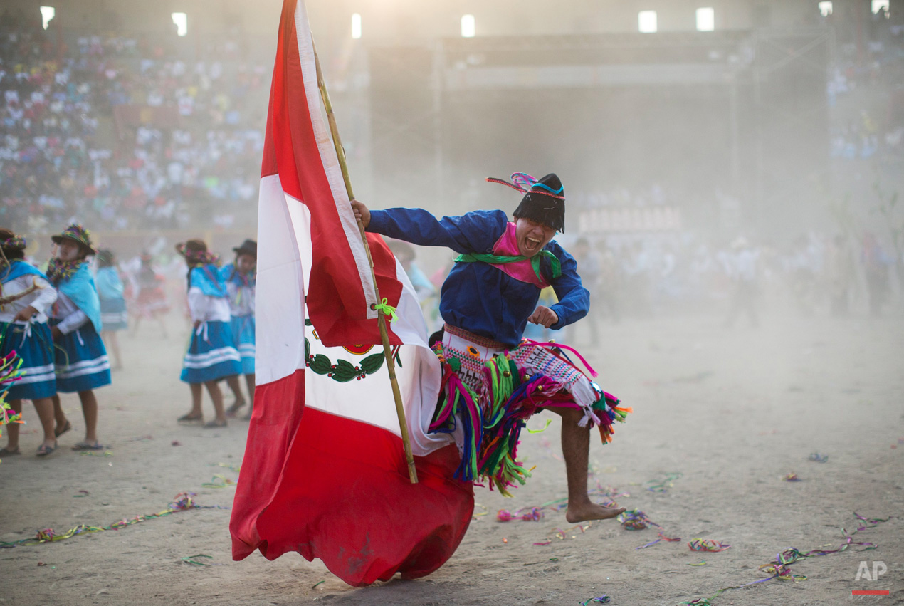 In this Sunday, March 29, 2015, photo, a man from the La Mar district of Ayacucho, sings in Quechua, holding a Peruvian national flag as he performs in the Vencedores de Ayacucho dance festival, in the Acho bullring in Lima, Peru. The different dance troupes that perform during the one-day competition typically bring a representation of Peru's national flag to assert their nationality as well as their ethnic background. (AP Photo/Rodrigo Abd)