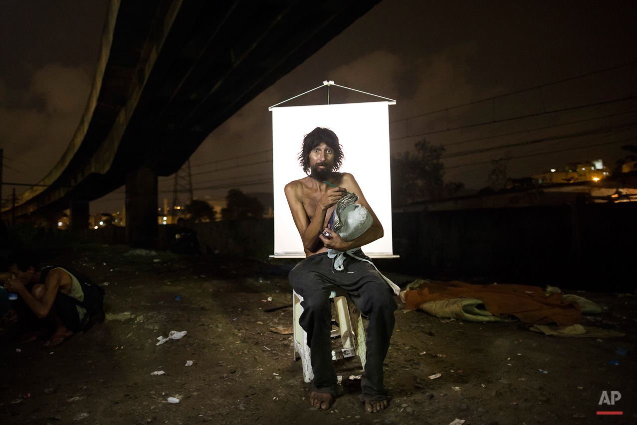 "In this March 17, 2015, photo, Renato Dias, 39, writes in his notebook as he poses for a portrait in an open-air crack cocaine market, known as a ""cracolandia"" or crackland, where users can buy crack, and smoke it in plain sight, day or night, in Rio de Janeiro, Brazil. Dias, who has been using crack for about 4 years, says he uses his notebook as a form of distraction. He writes about super heroes and dreams of becoming one. (AP Photo/Felipe Dana)"