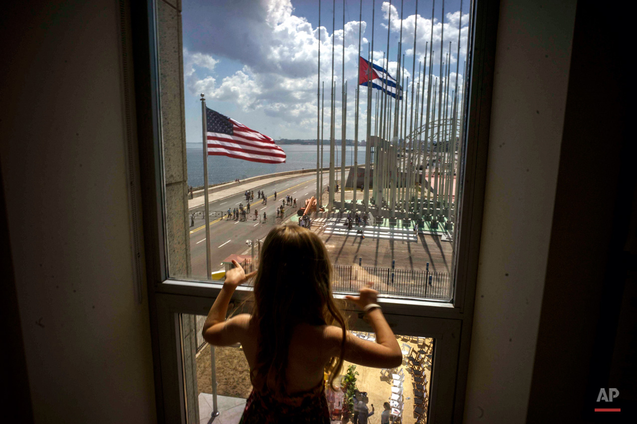 In this Aug. 14, 2015, photo, a girl looks out from the newly opened U.S. Embassy, overlooking the staging area, at the end of the flag raising ceremony in Havana, Cuba. Cuba and U.S. officially restored diplomatic relations July 20. (AP Photo/Ramon Espinosa)