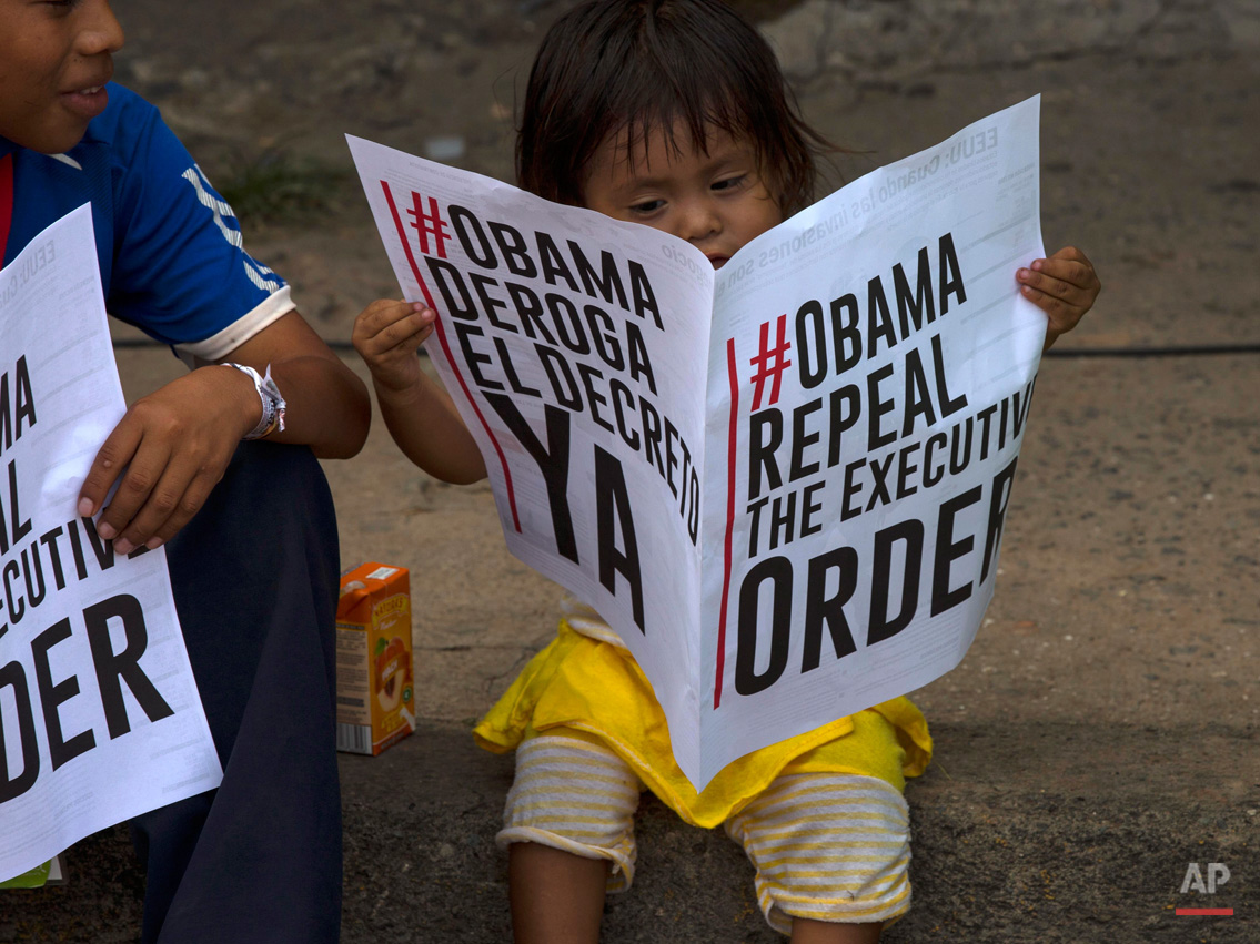 In this April 10, 2015, photo, a child reads a sign in favor of the U.S. repealing sanctions against Venezuela, before the arrival of Venezuela's President Nicolas Maduro to a monument honoring the victims of the 1989 U.S. invasion, in the Chorrillo neighborhood which saw the heaviest fighting during the invasion, in Panama City. Maduro said he planned to hand over about 10 million signatures to President Barack Obama during the Summit of the Americas, asking him to the repeal an order that froze the assets of seven Venezuelan officials for alleged human rights violations and corruption. (AP Photo/Ramon Espinosa)