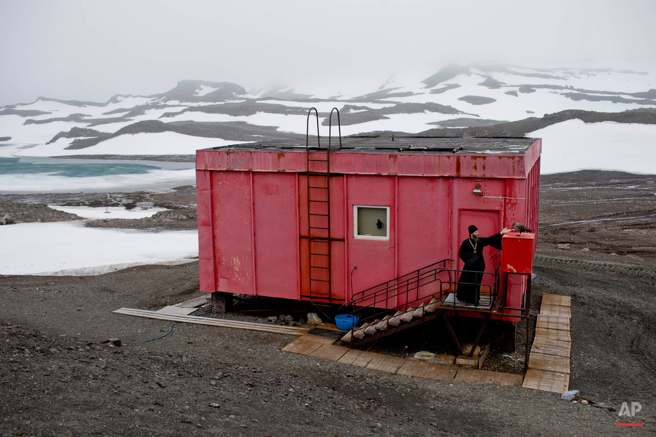 In this Feb. 1, 2015, photo, Russian Orthodox priest Sophrony Kirilov, 38, pets a Skua outside his home in King George Island, Antarctica. Penguins are his favorite animals, but Kirilov says he has also made friends with three large brown Skuas, Antarctic scavenging birds often seen hovering outside his doorstep in search of fresh fish caught by the priest. (AP Photo/Natacha Pisarenko)