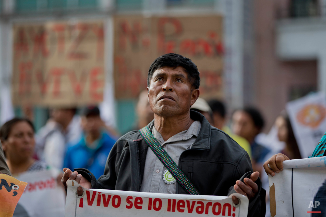 "In this March 10, 2015, photo, a demonstrator carries a sign that reads in Spanish: ""They took them alive, return them alive,"" in reference to 43 missing students from the Ayotzinapa rural teachers college, during a march to the private TV channel Televisa in Mexico City. The missing students' parents and supporters accuse national media outlets of decreasing their coverage of the missing students after statements by then-Attorney General Jesus Murillo Karam who said his investigators indicated all 43 students were killed by the Guerreros Unidos drug gang. The parents still have no concrete information on what happened to their children, and demand their voices be aired in order to continue the search for them. (AP Photo/Eduardo Verdugo)"