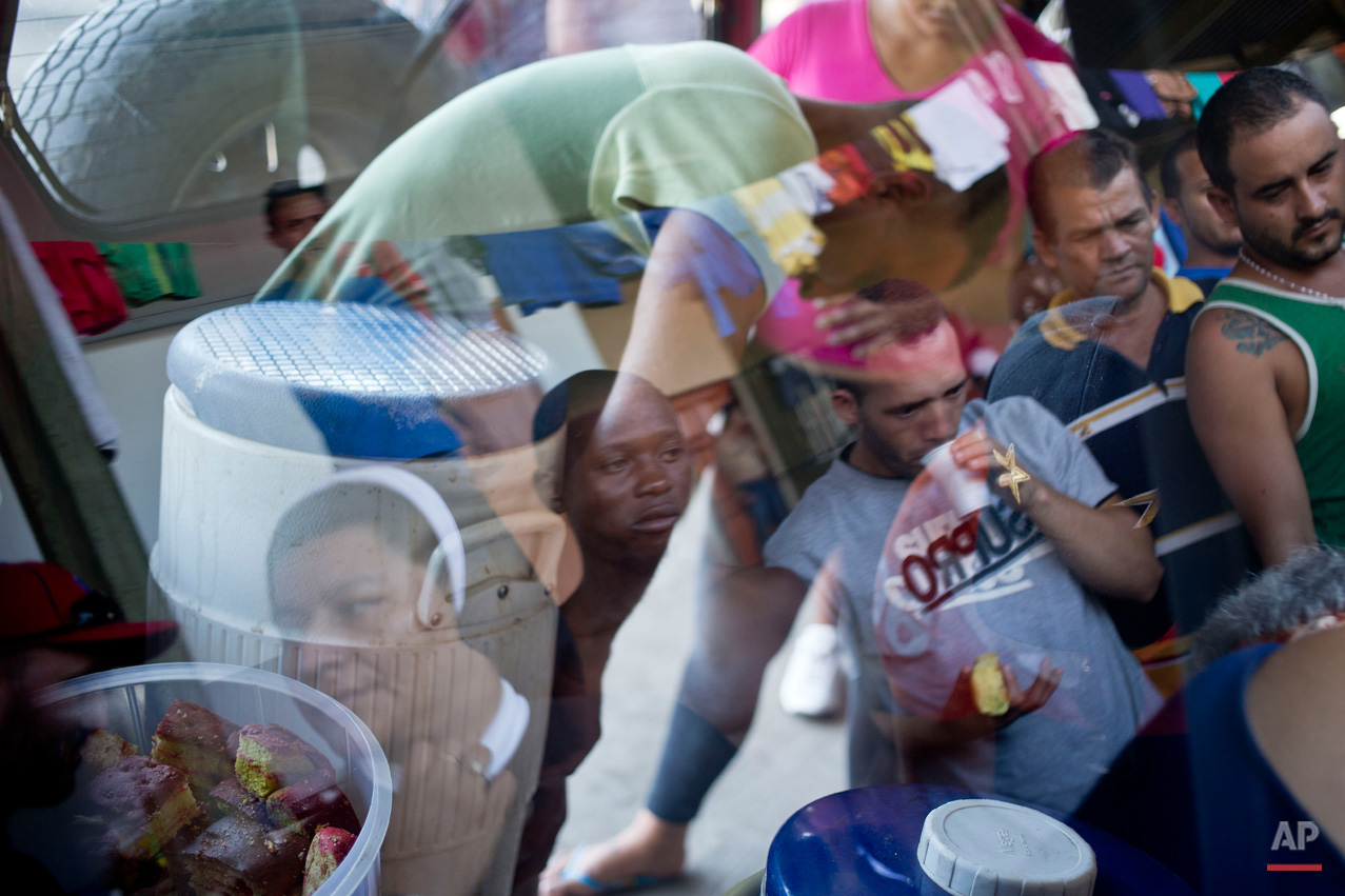 "In this Nov. 17, 2015, photo, Cuban migrants are reflected in the window of a nun's jeep, as they gather round for free breakfast items, near the immigration office in PeÒas Blancas, Costa Rica. More than 1,000 Cuban migrants heading north to the United States tried to cross the border from Costa Rica into Nicaragua, causing tensions to soar between the neighbors as security forces sought to turn them back. Nicaragua's government responded furiously on Sunday with a statement saying that Costa Rica ""had deliberately and irresponsibly thrown, and continues to throw"" the Cuban migrants into its territory, violating its national sovereignty. (AP Photo/Esteban Felix)"