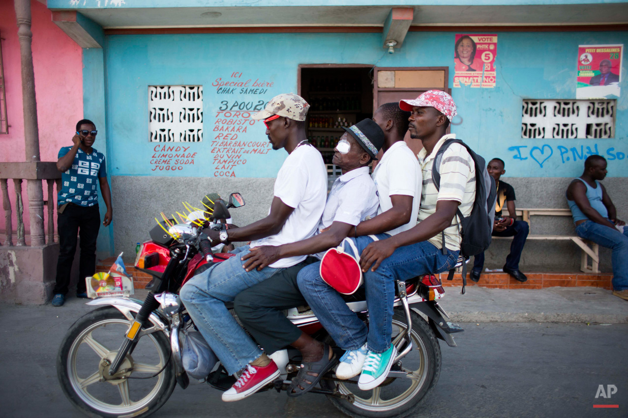 In Aug. 17, 2015, photo, Mathieux Saint Fleur, wearing a bandage over his eye, is sandwiched between the driver and his sons Renald St. Fleur, far right, and Jackilo Joseph, as they take a motorcycle taxi home after his cataract surgery in Cap-Haitien, Haiti. The 75-year-old had been virtually blind for two decades and was able to see again after surgery by volunteer eye doctors organized by the University of Utah's Moran Eye Center. (AP Photo/Dieu Nalio Chery)