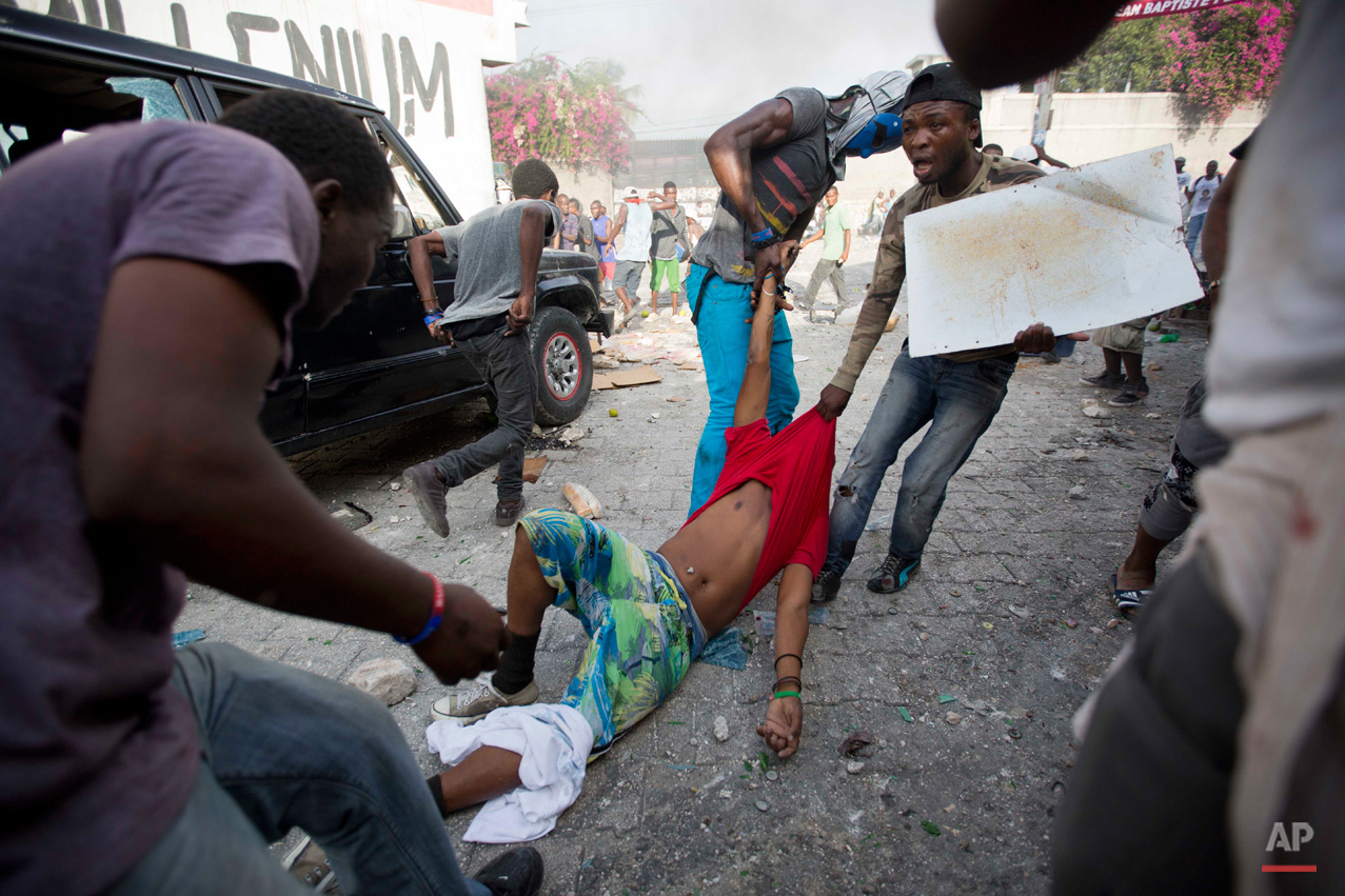 In this Nov. 20, 2015, photo, protesters drag to safety a fellow demonstrator injured by a machete when he was attacked by a resident in a neighborhood known for it's support of the ruling party, during a protest march against official preliminary election results, in Port-au-Prince, Haiti. Residents began throwing rocks at marchers as they made their way through the neighborhood. One protester was killed by a gunshot, when police intervened in the clashes between the residents and protesters. The presidential runoff election is Dec. 27. (AP Photo/Dieu Nalio Chery)