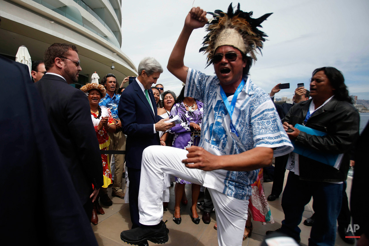 In this Oct. 5, 2015, photo, a man from Easter Island dances as U.S. Secretary of State John Kerry, behind, is given an Easter Island flag on the sidelines of the Our Ocean international conference on marine protection in Vina del Mar, Chile. President Barack Obama declared new marine sanctuaries in Lake Michigan and the tidal waters of Maryland on Monday, while Chile blocked off a vast expanse of the Pacific Ocean near the world-famous Easter Island from commercial fishing and oil and gas exploration. (AP Photo/Luis Hidalgo)