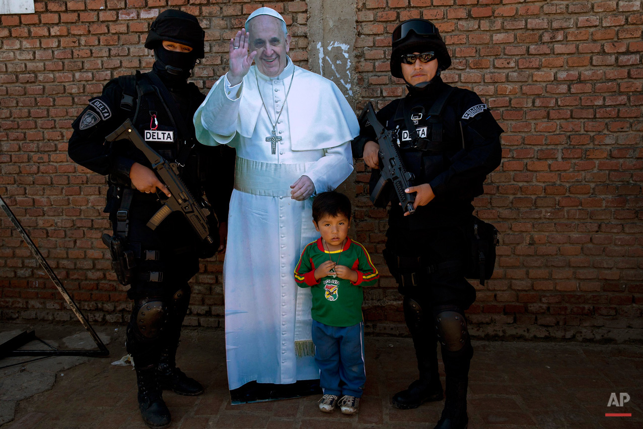 In this July 10, 2015, photo, Jair Ortega, age three, poses for a street photographer next to police special forces and a life-size cut out figure of Pope Francis, after the departure of the pope from Palmasola prison in Santa Cruz, Bolivia. Jair's mother asked the officers to pose with her son, saying he wants to be a police officer when he grows up. (AP Photo/Rodrigo Abd)