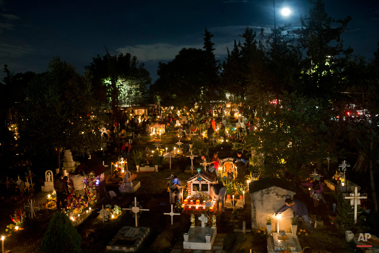 In this Nov. 1, 2015, photo, candles illuminate children's tombs in the San Gregorio cemetery during Day of the Dead festivities on the outskirts of Mexico City. In a tradition that coincides with All Saints Day and All Souls Day on Nov. 1 and 2, families decorate the graves of departed relatives with marigolds and candles, and spend the night in the cemetery, eating and drinking as they keep company with their deceased loved ones. At this cemetery, families pay a special tribute to children who have died, on the night of Oct. 31 into the morning of Nov. 1. The following night, families keep vigil at the tombs of adults. (AP Photo/Esteban Felix)