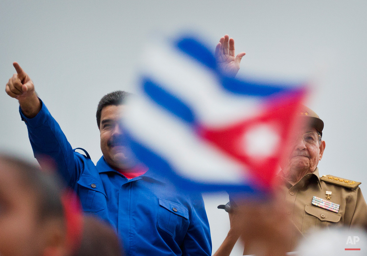 In this May 1, 2015, photo, Venezuela's President Nicolas Maduro, left, and Cuba' President Raul Castro acknowledge marchers as they parade past marking May Day in Revolution Square, in Havana, Cuba. Thousands of people converged on the plaza for the traditional march, led this year by the two leaders. (AP Photo/Ramon Espinosa)