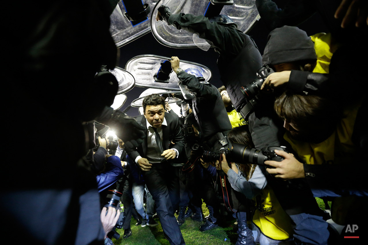 In this May 15, 2015, photo, Marcelo Gallardo coach of River Plate, center, leaves the field protected by riot police after the match against Boca Juniors was suspended during a Copa Libertadores soccer match in Buenos Aires, Argentina. Conmebol authorities and referee Dario Herrera canceled the game after pepper spray was thrown from the stands towards River Plate players, before the start of the second half of the game. (AP Photo/Victor R. Caivano)