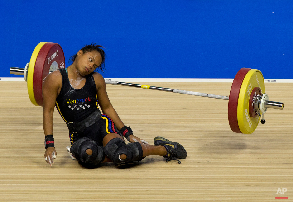 In this July 12, 2015, photo, Venezuela's Genesis Rodriguez Gomez collapses during a lift attempt in the women's 53kg weightlifting at the Pan Am Games in Oshawa, Ontario. Rodriguez took silver in the event. (AP Photo/Rebecca Blackwell)