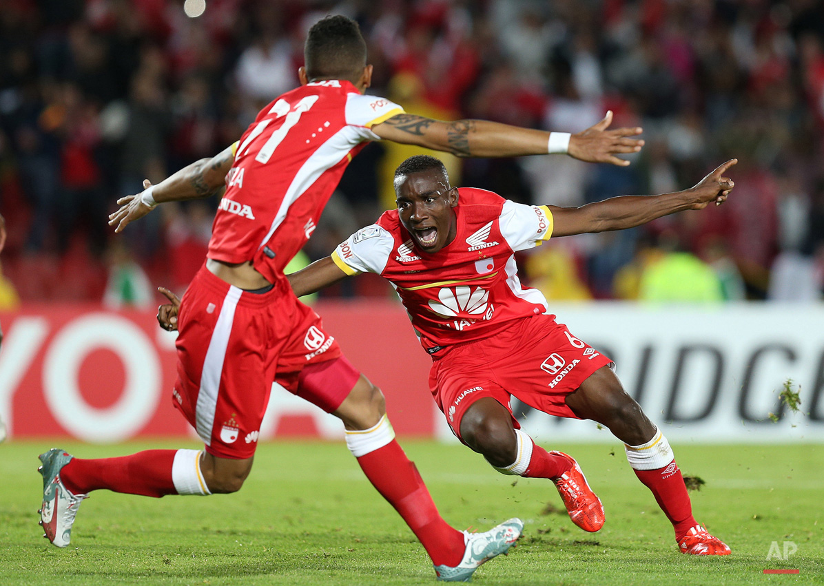 In this May 20, 2015, photo, Dairon Mosquera of Colombia's Independiente Santa Fe, right, celebrates scoring his side's first goal against Brazil's Internacional during a Copa Libertadores quarter finals first leg soccer match in Bogota, Colombia. (AP Photo/Fernando Vergara)