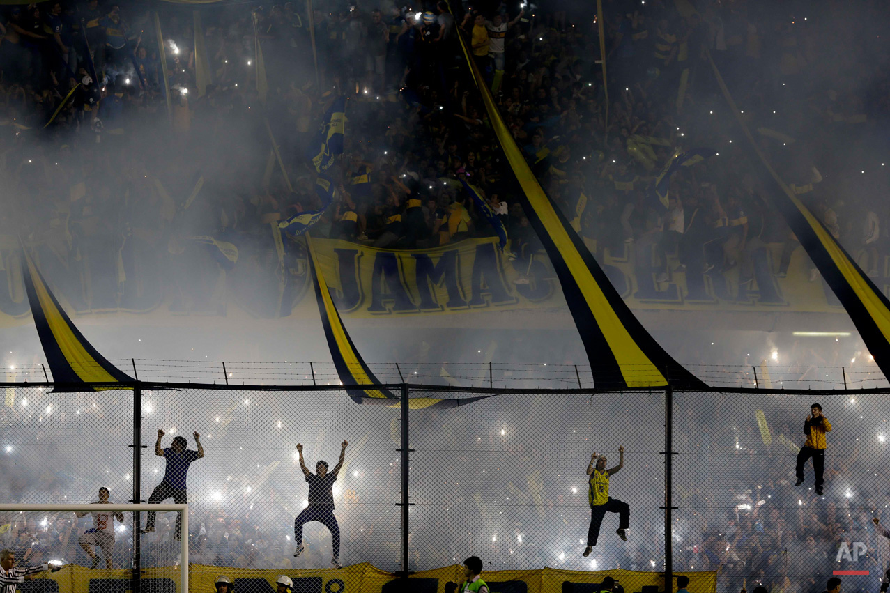 In this May 14, 2015, photo, Boca Juniors fans cheer their team before a Copa Libertadores round of sixteen soccer match against River Plate in Buenos Aires, Argentina. (AP Photo/Natacha Pisarenko)