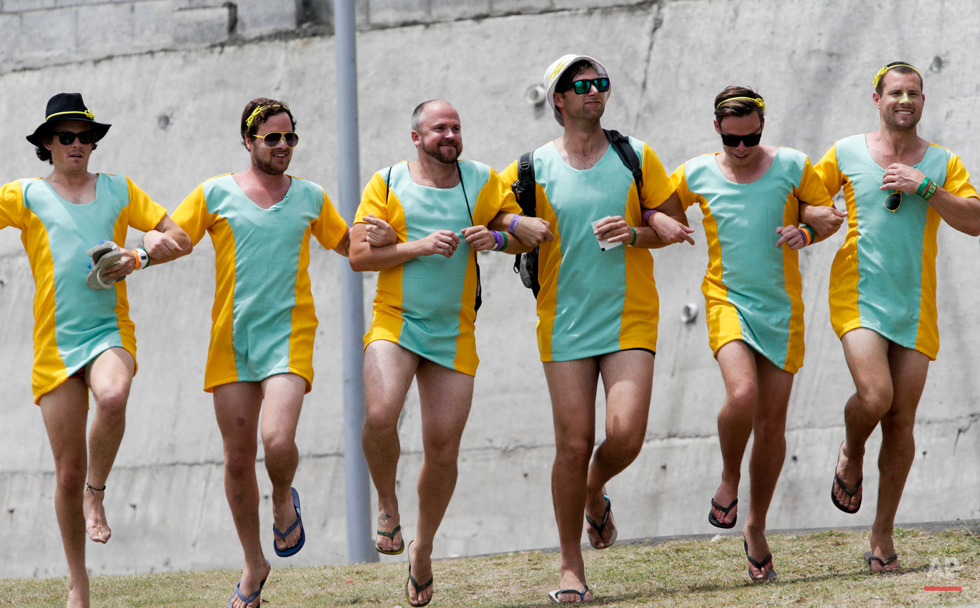 In this June 5, 2015, photo, Australian cricket fans dance arm in arm as they watch the second innings on the third day of the first cricket Test match between Australia and West Indies in Roseau, Dominica. (AP Photo/Arnulfo Franco)