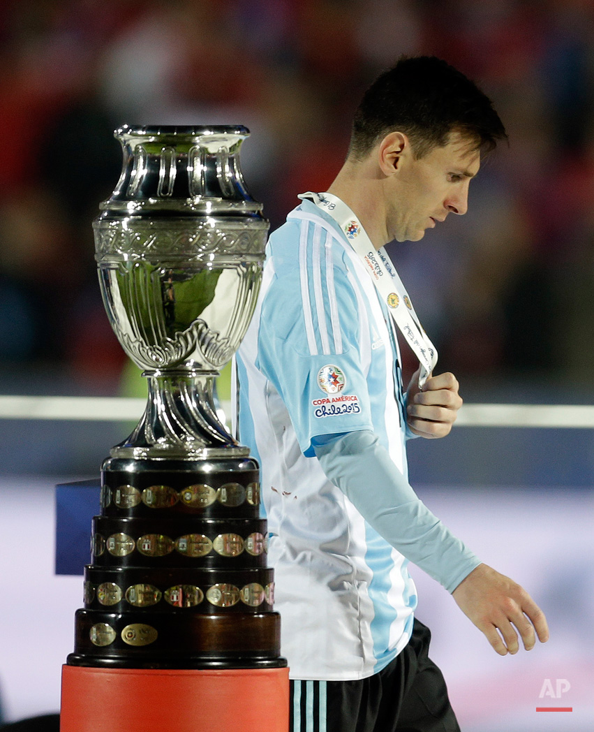 In this July 4, 2015, photo, Argentina's Lionel Messi walks by the Copa America trophy after receiving the silver medal after the final game with Chile at the National Stadium in Santiago, Chile. Chile goalkeeper Claudio Bravo made a save and striker Alexis Sanchez converted the winning penalty as host Chile defeated Argentina 4-1 in a shootout after a 0-0 draw in the Copa America final.(AP Photo/Natacha Pisarenko)