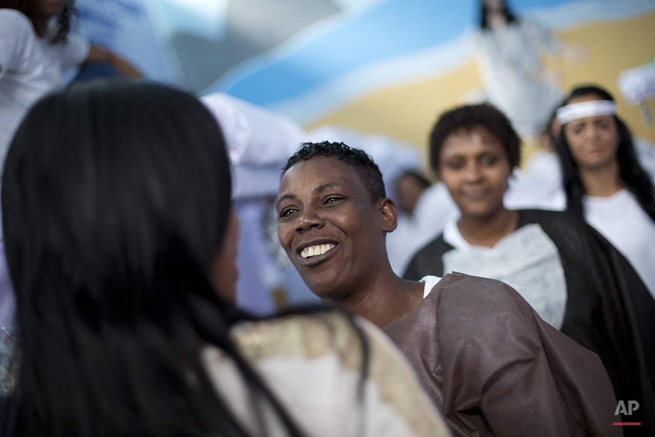 Prisoner smiles after performing during a Christmas decorating contest inside their cell at the Nelson Hungria prison in Rio de Janeiro, Brazil, Thursday, Dec. 10, 2015. Cleanliness was one of the criteria that the jury, made up of directors from area prisons, evaluated each of the nine cells on. Inmates from the winning cells scored prizes from coveted name-brand hair products to plastic stationary fans to a 21-inch flat-screen TV. (AP Photo/Silvia Izquierdo)