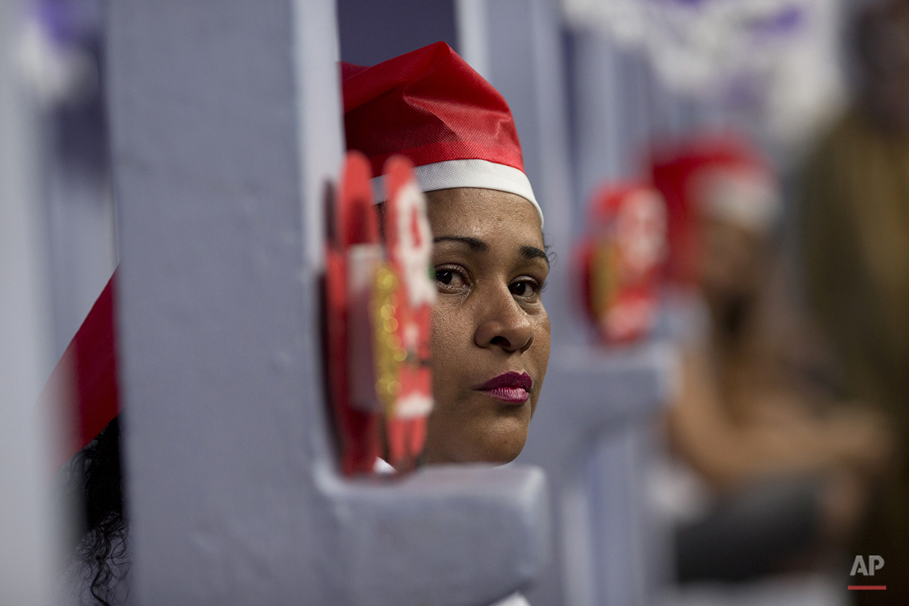 A prisoner watches other prisoners perform during a Christmas decorating contest inside their cell at the Nelson Hungria prison in Rio de Janeiro, Brazil, Thursday, Dec. 10, 2015. Inmates, overwhelming black and mixed-race women who are serving time for offenses from burglary to homicide, spent weeks decking out the cell blocks with holiday decorations they made themselves from the objects they have access to behind bars.(AP Photo/Silvia Izquierdo)