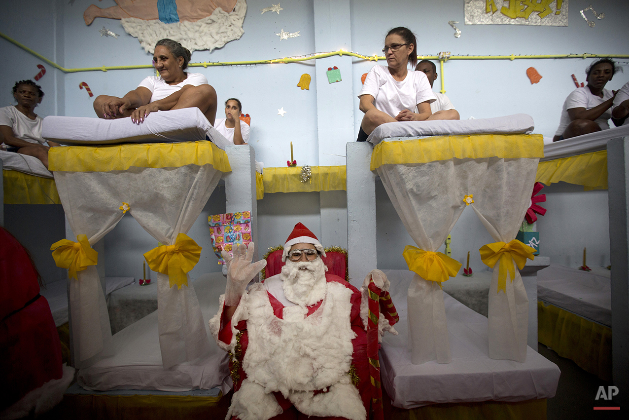 A prisoner dressed as Santa Claus sits on a bed during a Christmas decorating contest inside the Nelson Hungria prison in Rio de Janeiro, Brazil, Thursday, Dec. 10, 2015. Christmas trees were made from strips of green plastic from one-liter soda bottles; the presents below out of empty milk cartons swathed in tissue paper. (AP Photo/Silvia Izquierdo)