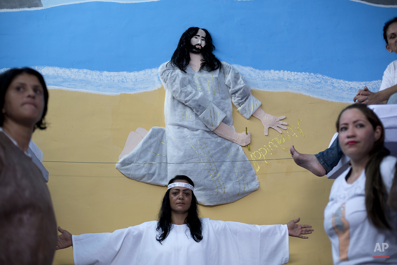 """Prisoners stand in front a painting of Jesus, that has real hair donated by a prisoner, and the word """"Acquitted"""" written in Portuguese, after performing in a Christmas decorating contest inside their cell at the Nelson Hungria prison in Rio de Janeiro, Brazil, Thursday, Dec. 10, 2015.  Inmates, overwhelming black and mixed-race women who are serving time for offenses from burglary to homicide, spent weeks decking out the cell blocks with holiday decorations they made themselves from the objects they have access to behind bars. (AP Photo/Silvia Izquierdo)"""
