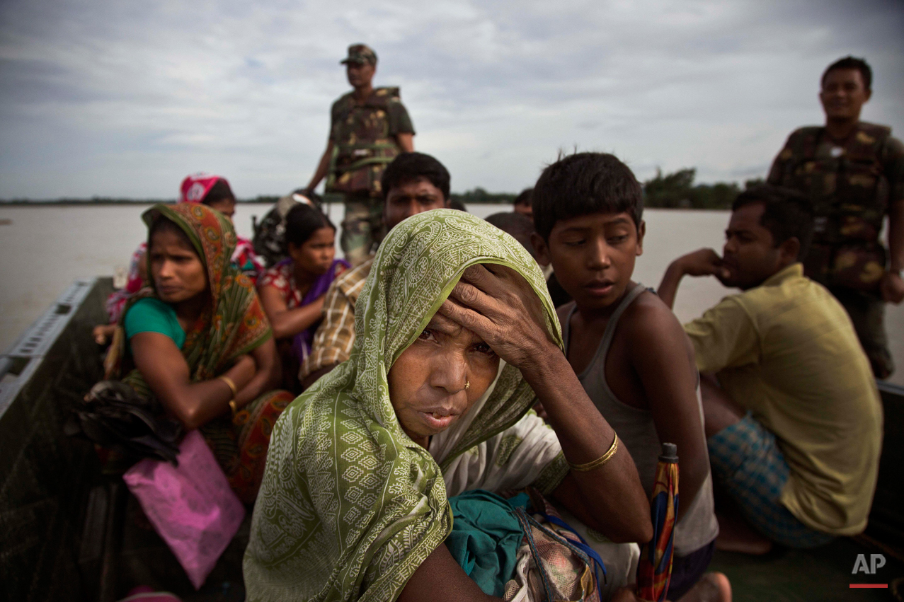 In this Aug. 21, 2015 photo, an Indian woman watches from an army boat as she along with others is transported to safer areas from flood affected Jaraguri village, about 160 kilometres (99 miles) west of Gauhati, India. Incessant rainfall in catchment areas have led to rise in water level of the Brahmaputra river and its tributaries, inundating several districts of both Upper and Lower Assam, according to local news reports. (AP Photo/Anupam Nath)