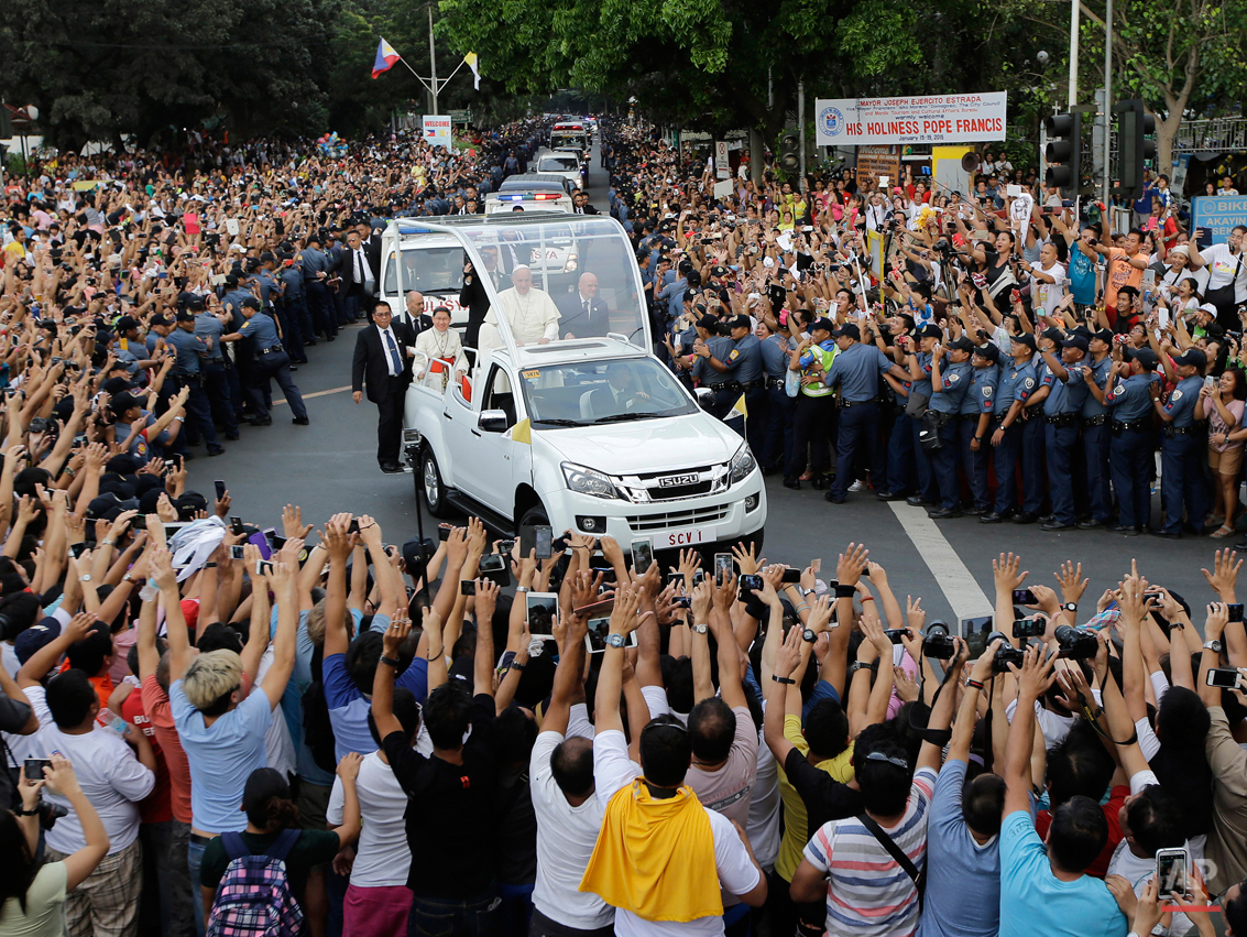 """In this Friday, Jan. 16, 2015 photo, Filipino Catholics take photos, using their phones and tablets, of Pope Francis aboard his Popemobile as his motorcade passes by on the way to another """"Meeting With Families"""" at the Mall of Asia Arena in Manila, Philippines. (AP Photo/Bullit Marquez)"""