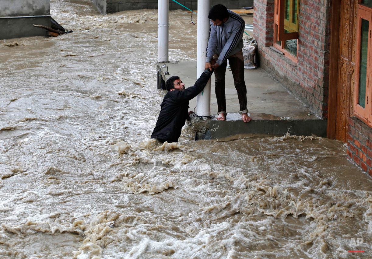 In this March 30, 2015 photo, a Kashmiri man stretches his hand to help a local evacuate from a flood affected area in Srinagar, Indian-controlled Kashmir. Hundreds of Kashmiris in both India and Pakistan moved to higher ground Monday as rain-swollen rivers swamped parts of the disputed Himalayan region placed under an emergency flood alert just six months after some 600 people died in flooding that left the region in shambles. (AP Photo/Mukhtar Khan)