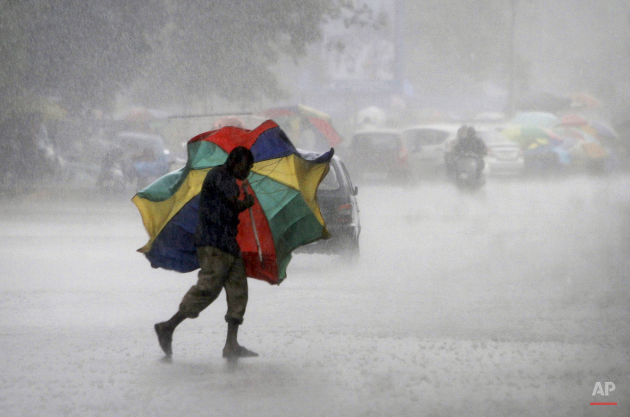 In this Friday, July 3, 2015, photo, a gust of wind bends the umbrella of a street vendor crossing the road during a heavy downpour in the eastern Indian city of  Bhubaneswar, India. (AP Photo/Biswaranjan Rout)