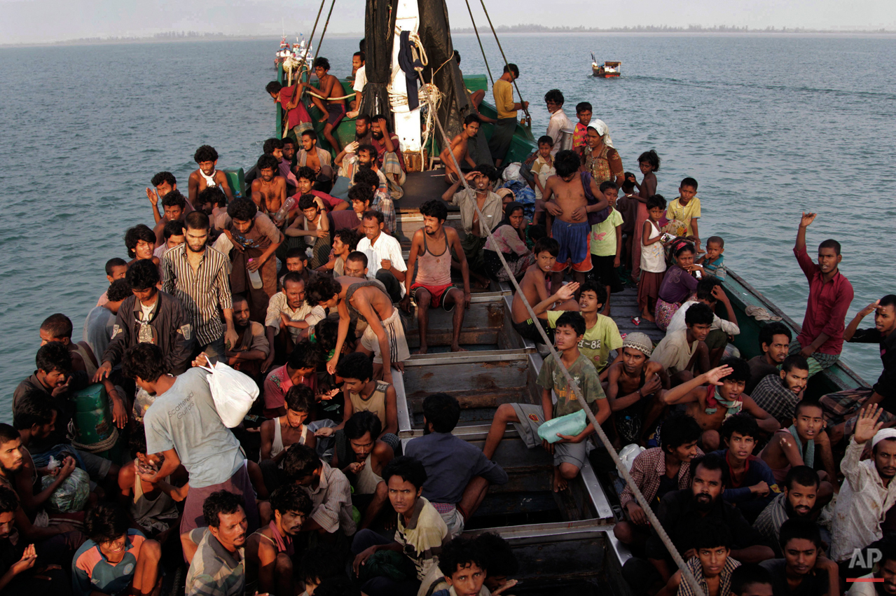 In this Wednesday, May 20, 2015, photo, migrants wait to be be rescued by Acehnese fishermen on their boat on the sea off East Aceh, Indonesia. Many of the thousands of migrants abandoned at sea in Southeast Asia this month are Rohingya Muslims who fled their home country of Myanmar. The Rohingya are a Muslim minority in predominantly Buddhist Myanmar, also known as Burma. Numbering around 1.3 million, they are concentrated in western Rakhine state, which neighbors Bangladesh. (AP Photo/S. Yulinnas)