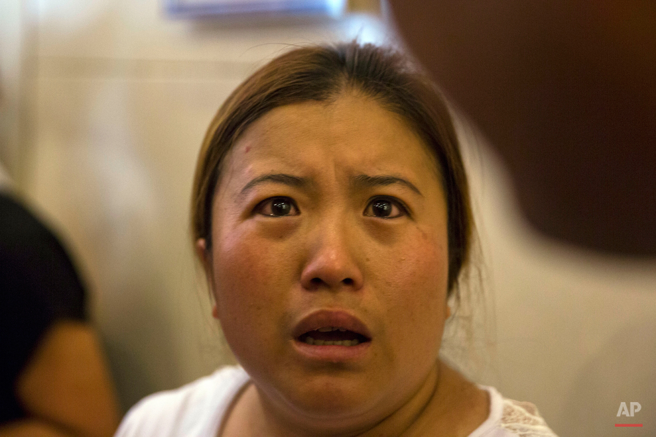 In this Saturday, Aug. 15, 2015 photo, Wang Baoxia talks to journalists about her missing brother Wang Quan who was at the scene of an explosion in northeastern China's Tianjin municipality. Angry family members of firefighters missing in the explosions that rocked the Chinese port city of Tianjin stormed a government news conference on Saturday, demanding information on their loved ones. (AP Photo/Ng Han Guan)