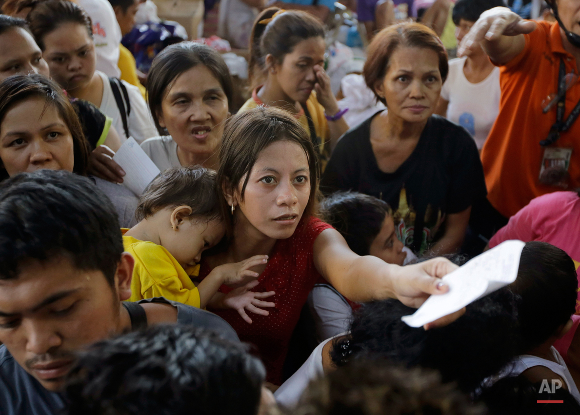 A mother, who lost her home in a huge fire on New Year's day, cuddles her baby as she lines up for a loaf of bread at an evacuation center near the site where hundreds of homes were destroyed along a creek Friday, Jan. 2, 2015 at suburban Quezon city, north of Manila, Philippines. The fire, believed to have been ignited by firecrackers, razed hundreds of homes Thursday in one of more than a dozen fires reported across the country as Filipinos welcomed the New Year. (AP Photo/Bullit Marquez)