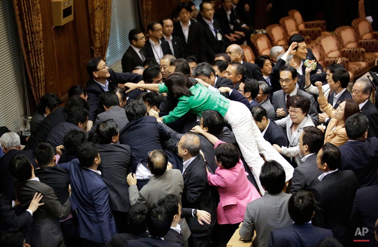 In this Thursday, Sept. 17, 2015 photo, opposition lawmakers surge toward the chairman's seat to protest as ruling party colleagues rush in to try to protect him during a committee voting of security bills at the upper house of the parliament in Tokyo. Japan's ruling Liberal Democratic Party pushed contentious security bills through a legislative committee, catching the opposition by surprise and causing chaos in the chamber. If the vote stands, the legislation will go to the upper house of parliament for final approval. (AP Photo/Eugene Hoshiko)